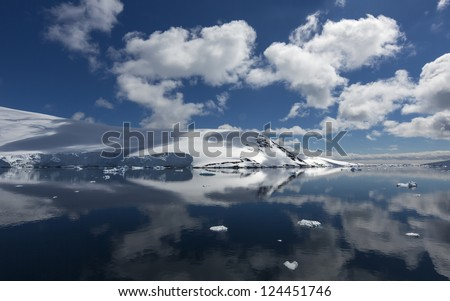 Bright sunny day in Antarctica. Full calm and reflection of icebergs in deep clear water. Travel by the ship among ices. Snow and ices of the Antarctic islands. - stock photo