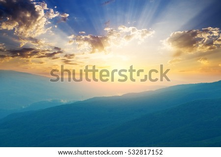 Bright sunrise in the mountains covered with fog.Relaxing views of the misty mountain valley and above it the rising sun.
