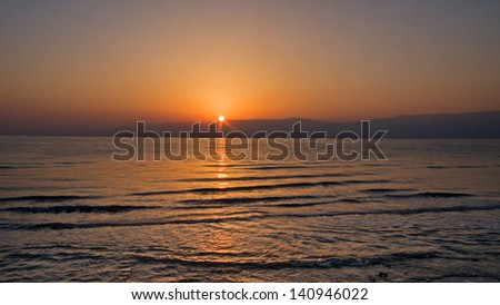 Bright sunrise over Jordan mountain Dead Sea shore with sun ray reflection on wavy water surface. Metzoke Dragot, Israel.