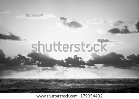 Bright sunrise over the ocean off Stradbroke Island, Queensland Australia in black and white - stock photo