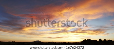Bright sunset in sky over New Zealand landscape  - stock photo