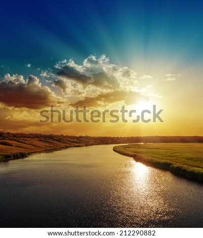 bright sunset over river with reflections - stock photo