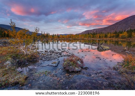Bright sunset skies reflected in Polygonal freshwater lake in Hibiny mountains above the Arctic Circle, Russia - stock photo