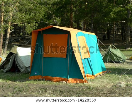 bright tent in the forrest on the grass - stock photo