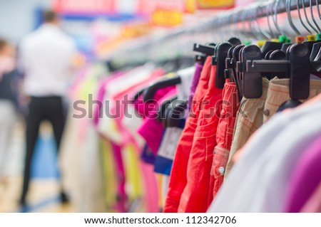 Bright trousers and t-shirts on stands in supermarket