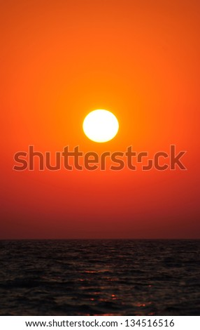 Bright vertical sunset under the sea surface - stock photo