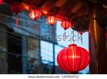 Bright vietnamese lanterns outside. Big red one and garland from small lanterns as decoration of wooden facade. Popular vietnamese decorative thing and souvenir. Symbols and traditions of country. - stock photo