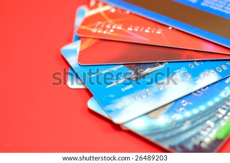 Bright wealth: macro of credit cards isolated on red background - stock photo