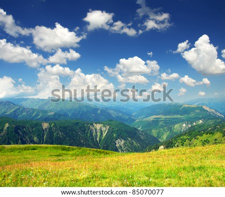 Bright white clouds and green meadow. Composition of the nature - stock photo