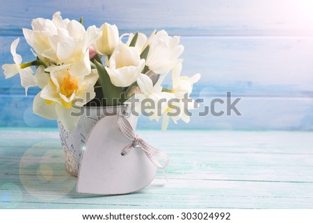 Bright white daffodils and tulips  flowers in bucket and decorative heart in ray of light on turquoise  painted wooden planks against blue wall. Selective focus. Place for text.  - stock photo