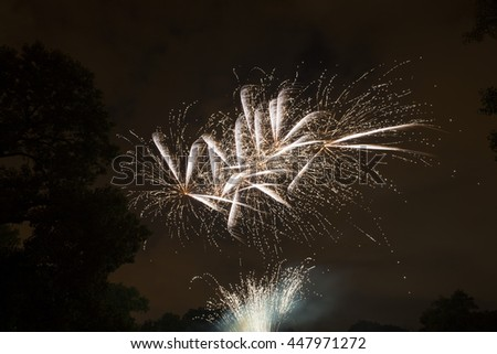 Bright white fireworks light up the sky in the Forest Glen neighborhood of Chicago - stock photo