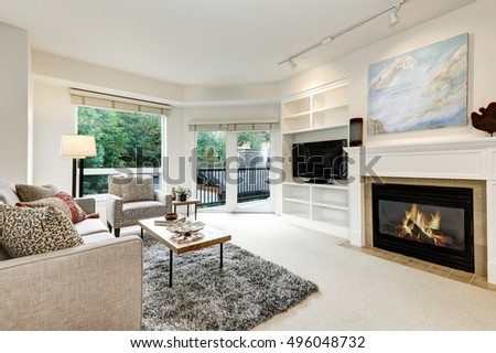 Bright White Living Room With Artificial Fireplace, Television And Cocktail  Table On Gray Fluffy Rug