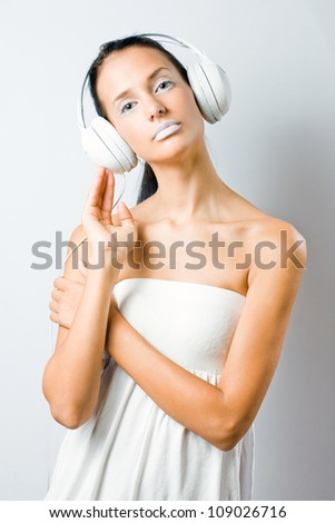 Bright white, portrait of gorgeous young brunette woman in creative makeup listening to music in white headphones.