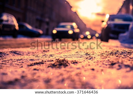 Bright winter sun in a big city, headlights of the approaching cars. View from the road level, image in the orange-blue toning - stock photo