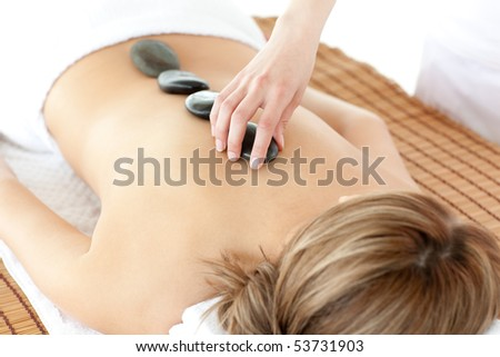 Bright woman having a stone therapy against a white background