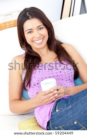Bright woman holding a cup of coffee smiling at the camera sitting on a sofa at home - stock photo