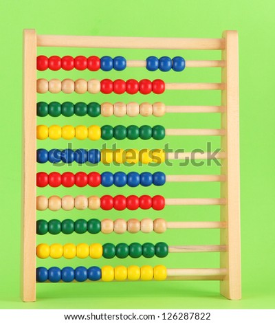 Bright wooden toy abacus, on green background