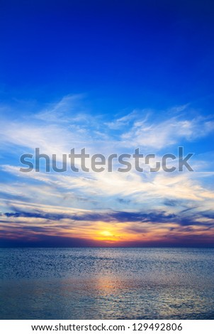 Bright yellow-blue sunset under the sea surface - stock photo