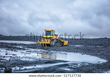 Bright yellow bulldozer against the cloudy sky in highland. Summer 2016 Iceland