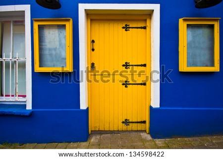 Bright yellow dutch door on blue facade - stock photo