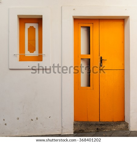 Bright yellow old door and a window of a typical house on Stromboli island, Sicily, Italy. - stock photo
