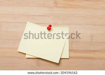 Bright Yellow paper blank with pin on wooden board