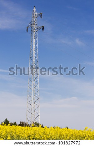 Bright yellow rape field with an electricity pylon in front of a blue sky with clouds - stock photo