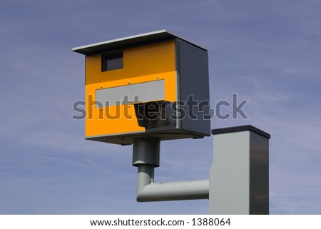 Bright yellow speed trap camera on grey / gray metal post. Blue sky background. - stock photo