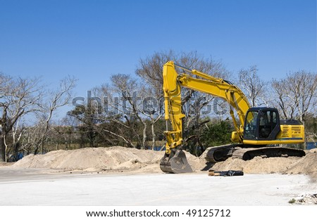 Bright yellow tract backhoe with blue sky - stock photo