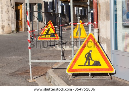 Bright yellow triangular warning signs for traffic at the foot of scaffolding erected for  repair to a building  obstructing a section of an urban street in a close up view - stock photo