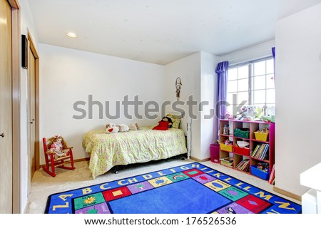 Bright young adult bedroom with carpet floor and blue rug, rustic bed, storage baskets and toys