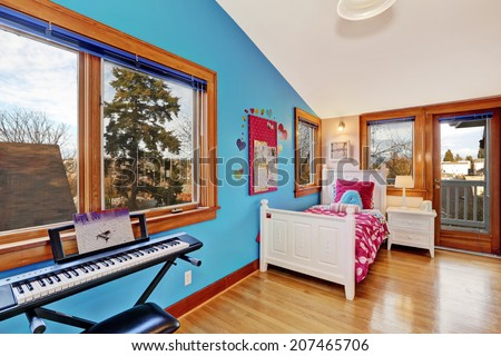 Bright young adult room with contrast blue wall and walkout deck. Furnished with white bed with nightstand and piano - stock photo