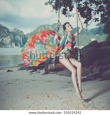Bright young lady on the beach a swing - stock photo