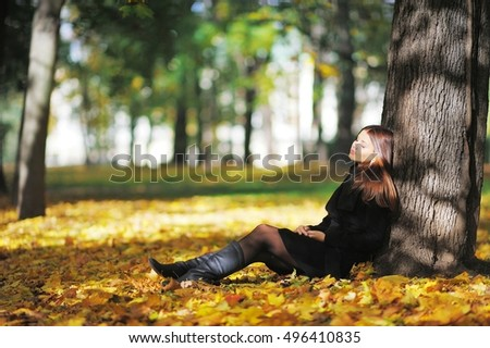 Bright young long-haired brunette sitting under a tree in yellow autumn maple leaves in a Park with closed eyes and dreams about something, side view.