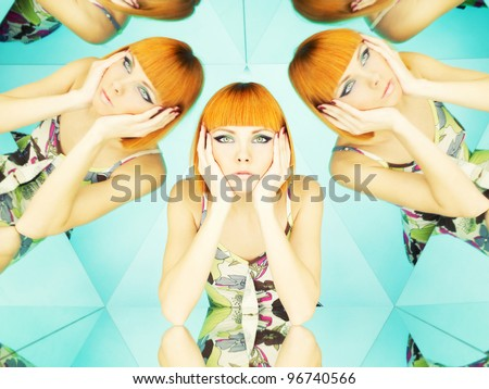 Bright young redhead woman in kaleidoscope of reflections - stock photo