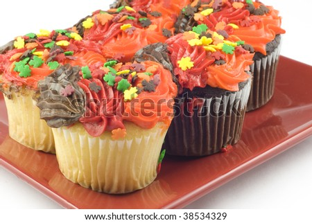 Brightly colored Autumn cupcakes with leaf shaped sprinkles, horizontal with copy space, selective focus - stock photo