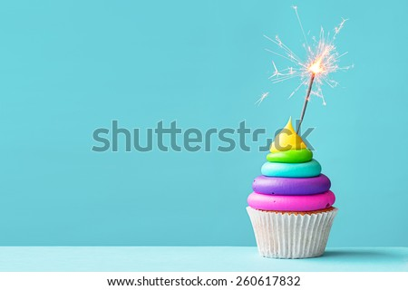 Brightly colored cupcake decorated with a sparkler - stock photo