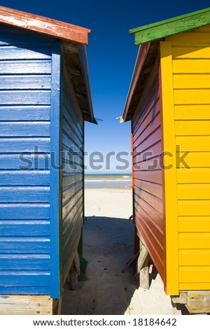 Brightly colored dressing huts on Muizenberg beach near Cape Town. - stock photo