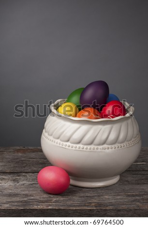 Brightly colored Easter Eggs on a grey background. Beautiful and traditional decoration with ample copy space. - stock photo