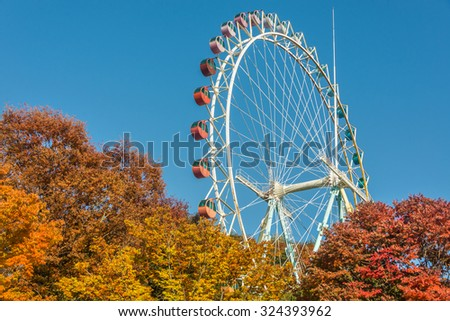 Brightly colored Ferris wheel against the blue sky and fall trees - stock photo