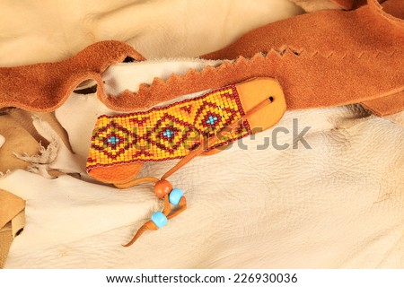 Brightly colored red, orange, yellow and turquoise beaded bracelet in Native American Pattern with scraps of buckskin and leather as background. - stock photo