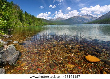 Brightly colored rocks seen through the crystal clear waters of Kintla Lake in Glacier National Park - USA - stock photo