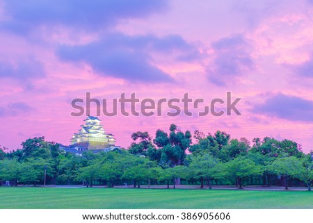 Brightly colored sunset sky behind Himeji-jo castle and green tree and grass foreground in Himeji, Japan reopened after 2015 renovations finished. Horizontal copy space