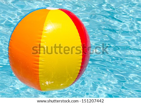 brightly coloured beach ball floating on clear blue water