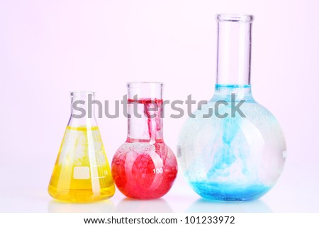 brightly ink in a flask with water on pink background