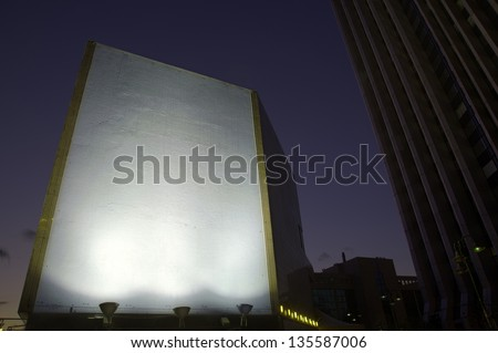 Brightly lit blank billboard stands out from the downtown area around at the early evening hours. Good as copy space for demonstrations etc. - stock photo