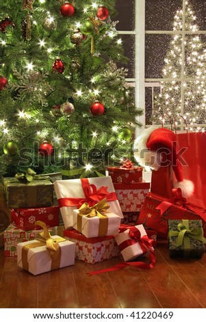 Brightly lit christmas tree with lots of gifts near window - stock photo