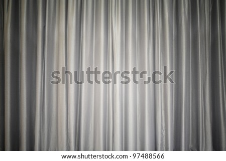 Brightly lit gray curtain for your background, like a theater stage - stock photo