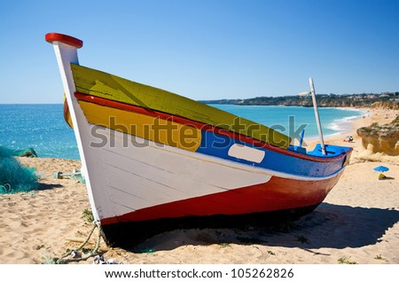 Brightly painted Iberian fishing boat on a sandy beach with a blue sea coastal background - stock photo
