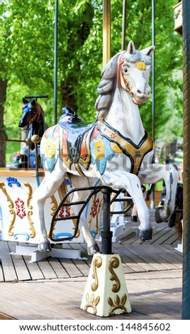 brightly painted old carousel horse in summer park - stock photo